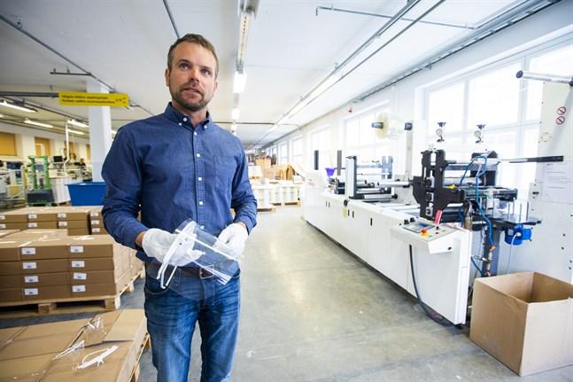 Fredric Tidström är vd på Orapac. Här är en bild från i våras när han står vid maskinen som stansar bland annat visir till vården. Lådorna i bakgrunden innehåller 1000 visir per låda.