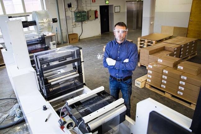 Fredric Tidström, vd vid Orapac, demonstrerar ett skyddsvisir som tillverkats för sjukhusen.  Han står vid maskinen som stansar visiren. Lådorna i bakgrunden innehåller 1 000 visir per låda.