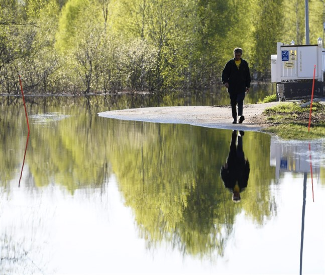 Markku Lemmetty går hem längs sin gata i Rovaniemi. Vattnet är inte längre lika djupt som det var för några dagar sedan.