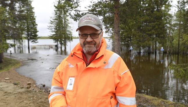 Mauri Kivelä är fastighetschef i Kittilä. Här står han på vallen som ska skydda äldreboendet från vattenmassorna. Men parkeringsplatsen täcks nu av vatten.