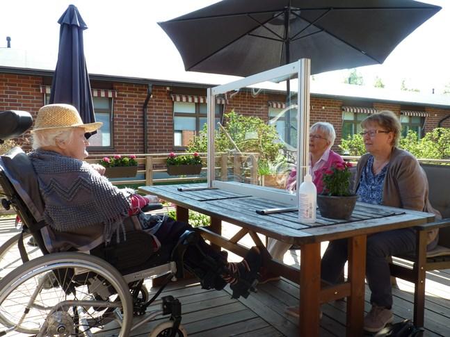 Systrarna Benita Renlund och Gunborg Ingers kan tryggt sitta ute och prata med sin mamma Gunvor Snellman vid Pedersheim tack vare plexiglaset mellan dem.