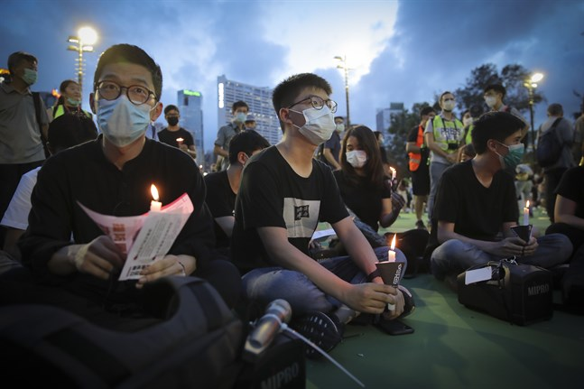 Den framträdande demokratiaktivisten Joshua Wong (mitten) är en av de som samlats för ljusmanifestationen för massakern på Himmelska fridens torg.