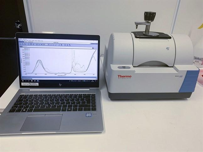 En infrarödspektroskopiapparat mäter virusförekomsten i ett coronaprov.