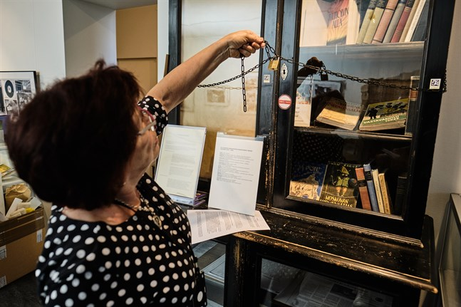 """Anneli Ketonen visar det speciella skåp där förbjudna böcker låsts in. Finlands biblioteksmuseiförening i Vasa får bidrag för utställningen """"Förbjudna böcker""""."""