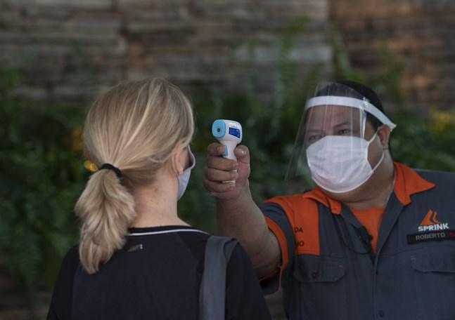 En kvinna kontrolleras för feber innan hon får gå in i en affär i Rio de Janeiro i Brasilien.