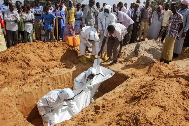 Vårdpersonal i skyddsutrustning vid en begravning av en man som dött i covid-19 på en kyrkogård i Somalias huvudstad Mogadishu. Arkivbild.