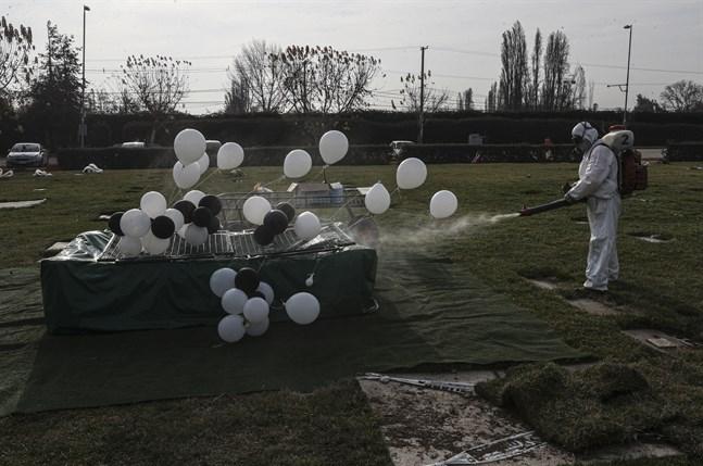 En kyrkogårdsarbetare med skyddsutrustning desinficerar gravar i Santiago, Chile.