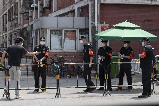 Säkerhetspersonal vid ett kvarter som stängts ned i Peking i samband med ett utbrott av det nya coronaviruset.