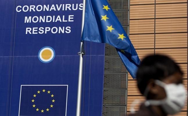 En kvinna med andningsskydd passerar EU-högkvarteret i Bryssel. Arkivbild.