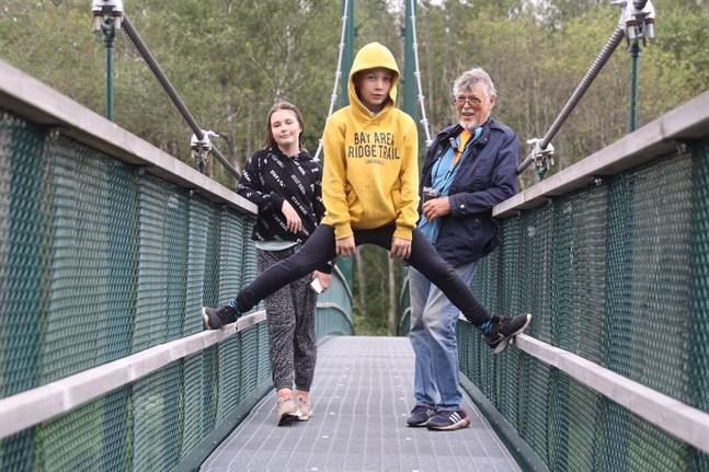 Camilla, Calle och Canne Lundberg på hängbron över Tjöck å. Barnbarnen Camilla och Calle bor i St Karins men var på besök hos farfar Canne och farmor Barbro i Kristinestad.