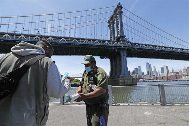 En parkvakt delar ut munskydd vid parkområdet under Brooklyn Bridge i New York.