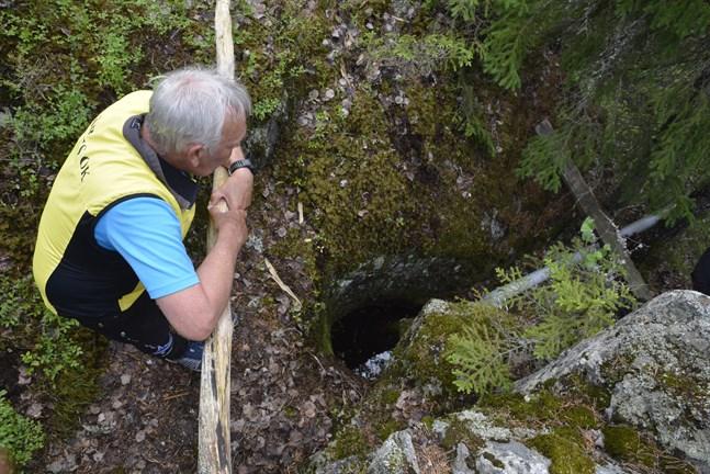 Karl-Gustav Norrgrann blickar ner i jättegrytan som uppkom under istiden. Den är som bäst fylld med vatten men det finns en pump att få bort vattnet med. Då får man se den jämna bottnen.