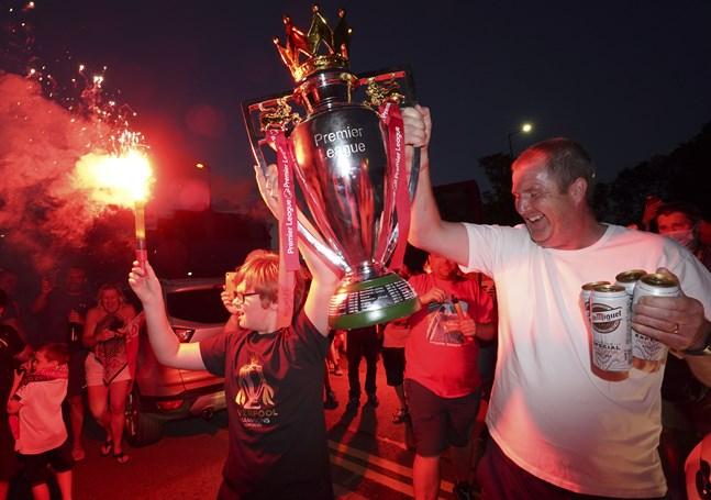 Liverpoolsupportrar firar med en kopia av Premier League-pokalen utanför hemmaarenan Anfield efter det att klubbens första ligatitel på 30 år blivit klar.