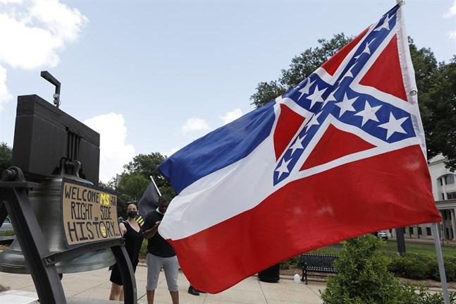 Mississippis flagga vajar utanför delstatens Capitolium i Jackson. Bakom den syns demonstranter som stödjer att flaggan ändras.