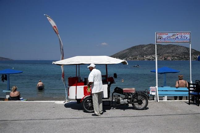 En glassförsäljare i väntan på kunder på ön Salamina strax väster om Aten på måndagen.