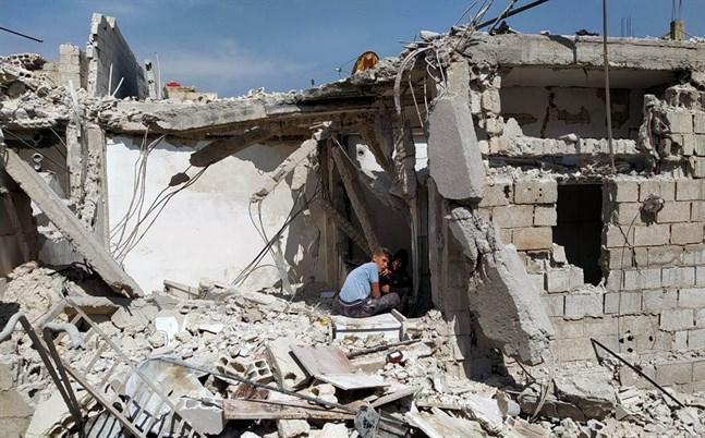 Pojkar leker i en ruin i en förort till det krigshärjade Syriens huvudstad Damaskus.