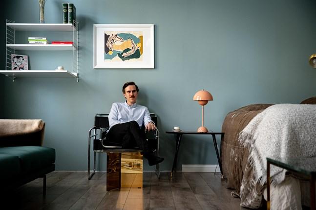 Matias Mäkynen i småbarnsfamiljens sparsamt inredda rum som fungerar som sovrum och vardagsrum samtidigt.