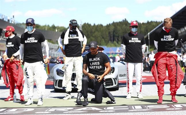 Lewis Hamilton knäböjer inför F1-premiären i Österrike.