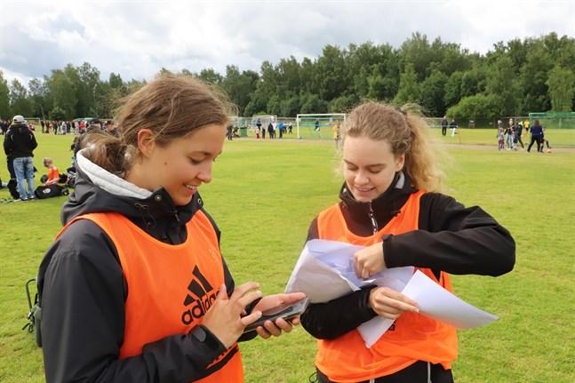 Planvakterna Sofia Morney och Evelina Myntti har fullt upp med att samla och ringa in resultaten i Wasa Football Cups matcher.