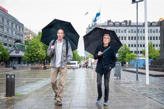Jukka Kankaanpää, till vänster, och Gunnar Bäckman visar fotografier på en utställning utomhus i Vasa centrum.