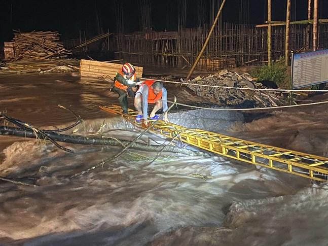 En räddningsarbetare hjälper en man att korsa ett översvämmat område i den kinesiska provinsen Jiangxi.