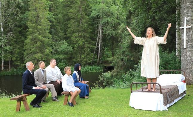 Fok hör förundrat på när Maria Åkerblom plötsligt reser sig från sin sjukbädd och börjar predika.