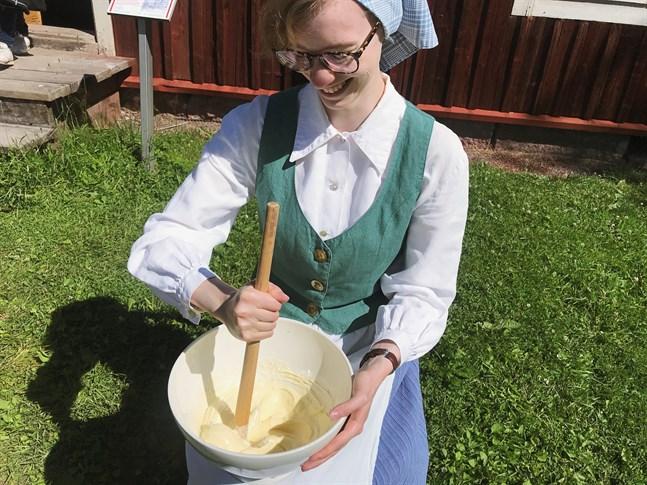 Dagen till ära är guiderna på Stundars klädda i gammaldags kläder. Här visar Annika Mäenpää hur man kärnar smör.