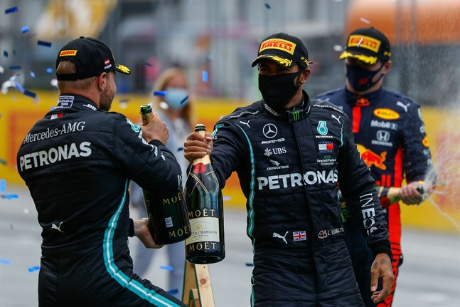 Valtteri Bottas gratulerar stallkamraten Lewis Hamilton till segern. I bakgrunden Max Verstappen.