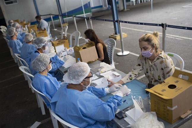 Vårdarbetare tar blodprover vid en testplats i Rio de Janeiro i Brasilien.