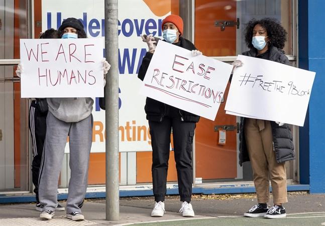 Kvinnor protesterar mot de nya virusrestriktionerna vid ett drabbat bostadskomplex i Melbourne den 6 juli.