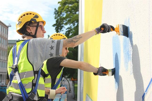 Valentina Gelain är en av konstnärerna bakom muralmålningen på Vasa Övningsskolas gymnasium. Bakom syns Bekim Hasaj.