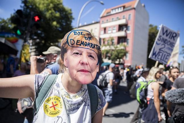 """En demonstrant har skrivit orden """"hej då demokrati"""" på en mask föreställande den tyska förbundskanslern Angela Merkel."""