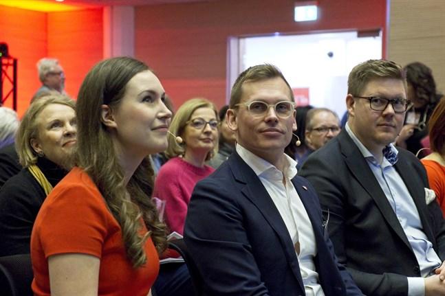 Socialdemokraternas partisekreterare Antton Rönnholm (mitten) medger med glädje att den nuvarande regeringens linje skiljer sig från oppositionens linje. Till vänster statsminister Sanna Marin, till höger riksdagsledamot Antti Lindtman.