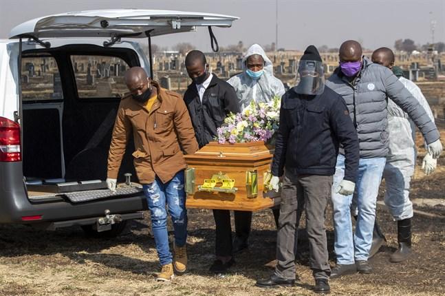 Familjemedlemmar och begravningsarbetare begraver en avliden i covid-19, i Thokoza, öster om Johannesburg, den 23 juli.