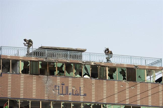 Afghanska säkerhetsstyrkor ovanpå ett tak i anslutning till det attackerade fängelset i staden Jalalabad.