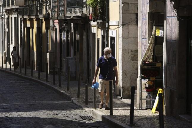 En man iförd munskydd promenerar längs en gata i Portugals huvudstad Lissabon. Arkivbild.