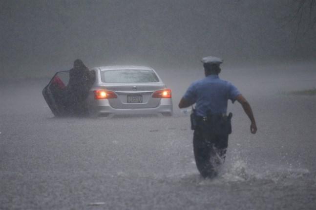 Polis rycker ut för att hjälpa en bilist som fastnat i vattenmassorna i Philadelphia.