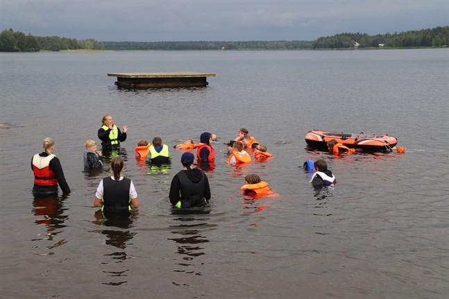 Simskoleeleverna prövar på att flyta och simma med flytväst.