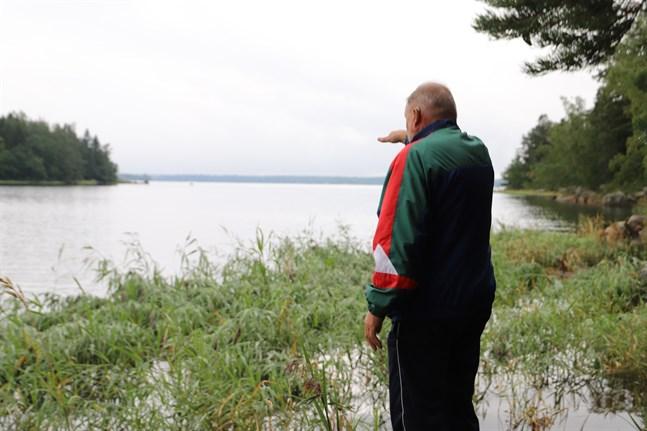 Martin Bäck pekar ut över Skinnarfjärden. Väldiga mängder av ålnate har flutit upp på stränderna i hela Skinnarfjärden.