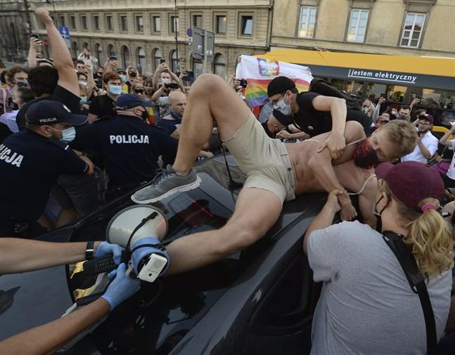 En aktivist klättrar upp på en polisbil under demonstrationen i Warszawa i fredags.