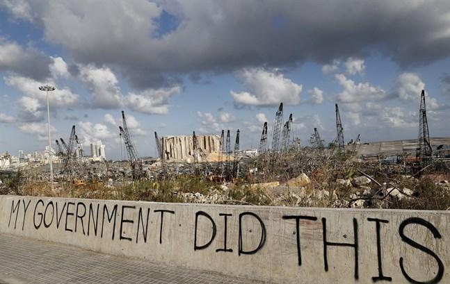 """""""Min regering gjorde det här"""", står det på en mur framför förödelsen efter explosionen i Beirut."""