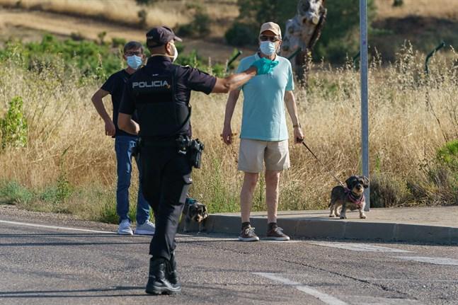 Myndigheterna i Spanien reagerade för sent men nu tas krisen på allvar och alla hjälps åt, skriver Ellinor Granholm om hur man hanterat coronapandemin i Spanien. På bilden pratar en polis med två män vid en vägspärr i Aranda de Duero nära Burgos, den 7 augusti. Då infördes en två veckors lockdown för att försöka begränsa spridningen av covid-19 i regionen.