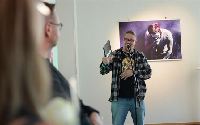Bandmedlemmen Jesse Nissinen visar upp fotoboken som 1G3B som nyss kommit från tryckeriet. I förgrunden fotografen Bengt Henriksson, vars bilder av 1G3B nu visas i Närpes.