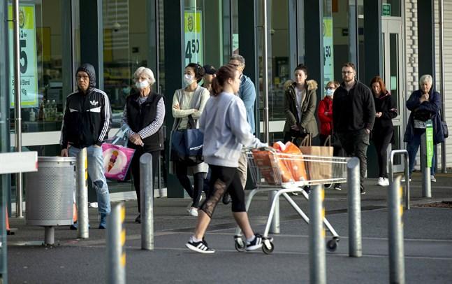 Människor köar utanför en livsmedelsbutik i Auckland.