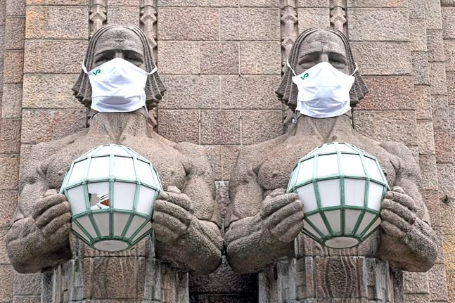 Statyerna utanför järnvägsstationen i Helsingfors fick munskydd efter att Institutet för hälsa och välfärd utfärdat en allmän rekommendation om att bära munskydd i kollektivtrafiken.