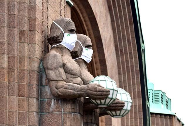 Institutet för hälsa och välfärd utfärdade på torsdagen en rekommendation om att använda munskydd i kollektivtrafiken och på offentliga platser där man inte kan hålla ett säkerhetsavstånd till andra människor. Statyerna vid järnvägsstationen i Helsingfors föregår med gott exempel.