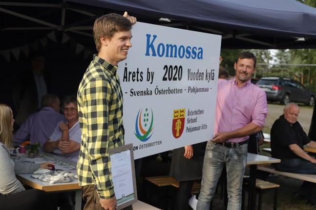 Gabriel Ståhlberg och Kjell Engström med Årets by-skylt.