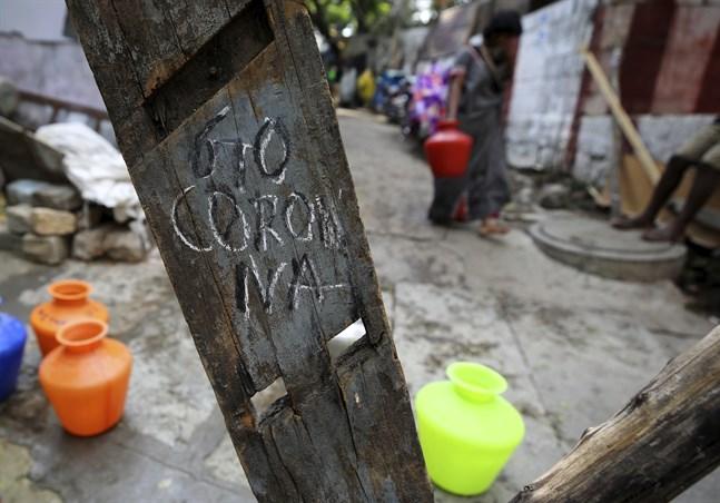 """""""Go Corona"""" står skrivet på ett plank i ett slumområde i den Indiska staden Bangalore."""