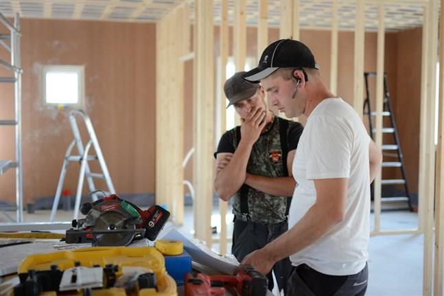 Mattias Granholm bygger både sitt eget hus och grannarnas. Här funderar han på lösningar i granngården tillsammans med grannen och barndomskompisen Patrik Skrifvars.