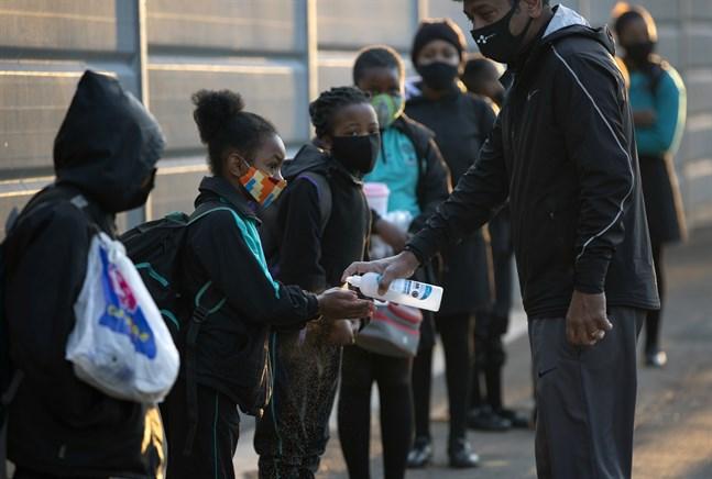 Elever spritar sina händer i samband med att de deras skola återöppnar i Johannesburg, Sydafrika.